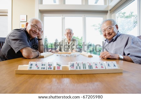 Portrait of three elderly men sitting at table playing game - stock photo
