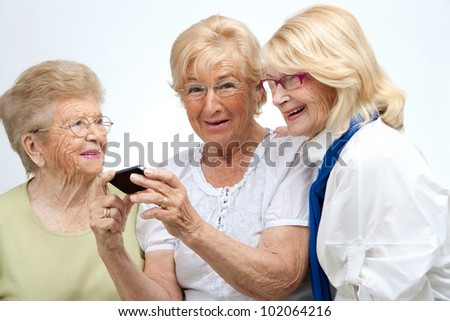 Portrait of three elderly senior woman holding cell phone.Isolated on white.