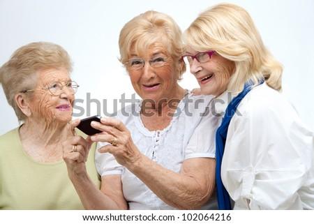 Portrait of three elderly senior woman holding cell phone.Isolated on white. - stock photo