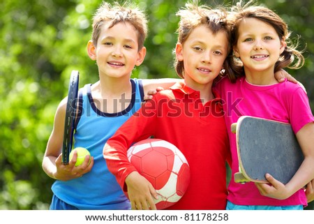 Portrait of three embracing children with sports equipment - stock photo