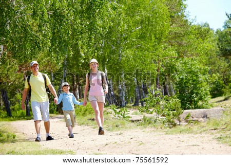 Portrait of three family members walking down road at summer