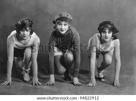 Portrait of three female runners in starting position - stock photo