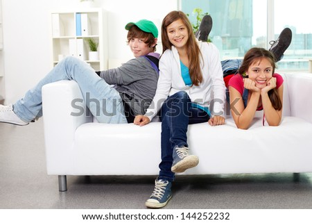 Portrait of three friends sitting on sofa, looking at camera and smiling - stock photo