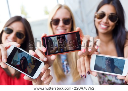 Portrait of three friends taking photos with a smartphone - stock photo