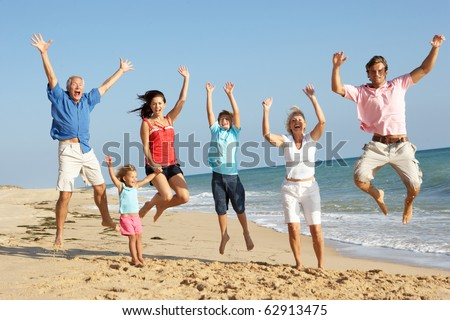 Portrait Of Three Generation Family On Beach Holiday Jumping In Air - stock photo
