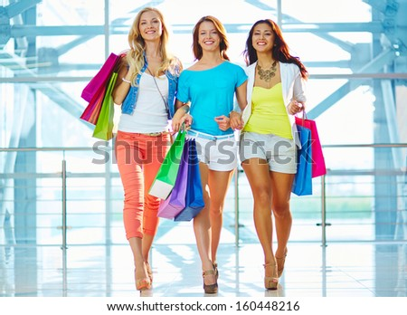 Portrait of three glamorous girlfriends with paperbags after shopping in trade center - stock photo