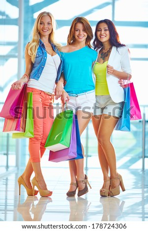 Portrait of three glamorous girlfriends with paperbags looking at camera after shopping - stock photo