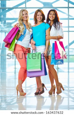 Portrait of three glamorous girlfriends with paperbags looking at camera in the mall - stock photo