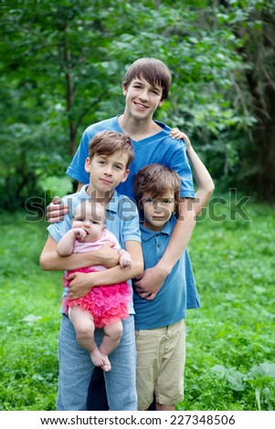 Portrait of three happy brothers and sisters in summer park - stock photo