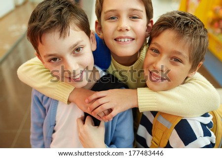 Portrait of three happy embracing boys - stock photo