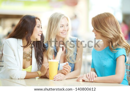 Portrait of three happy girls chatting while having drink after shopping - stock photo