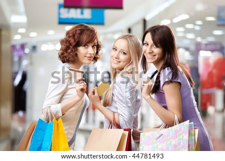 Portrait of three happy girls in shop, with three credit cards in hands - stock photo