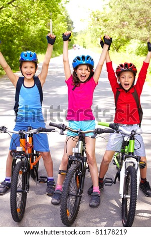 Portrait of three happy little cyclists - stock photo