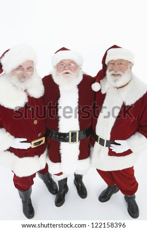 Portrait of three happy senior Santa Claus standing together isolated over white background - stock photo