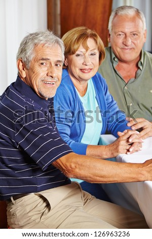 Portrait of three happy seniors sitting at table in a rest home - stock photo