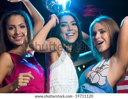 Portrait of three laughing girls dancing at disco in the night club