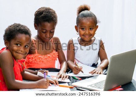 Portrait of three little African girl fiends spending time together drawing with crayons and laptop.Isolated on light background.