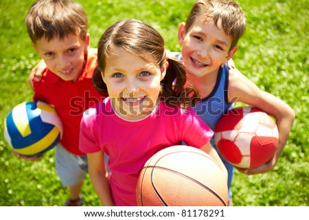 Portrait of three little children with balls looking at camera and smiling - stock photo
