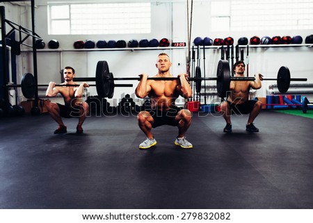 Portrait of three man at gym training clean and jerk - stock photo