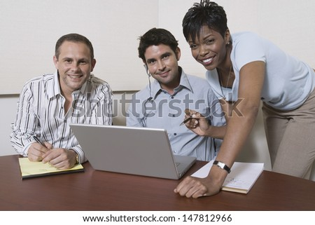 Portrait of three multiethnic businesspeople using laptop at office desk - stock photo