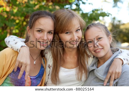 Portrait of three pretty student girls in the park