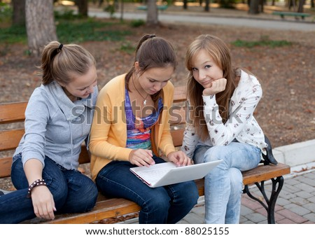 Portrait of three pretty student girls in the park and surfing the internet - stock photo