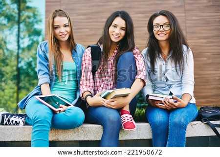 Portrait of three pretty students smiling at camera