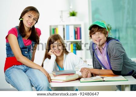 Portrait of three smart classmates looking at camera in classroom - stock photo