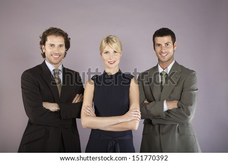Portrait of three smiling business people standing with arms crossed against purple background - stock photo
