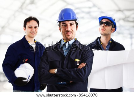 Portrait of three smiling engineers in a contruction site - stock photo
