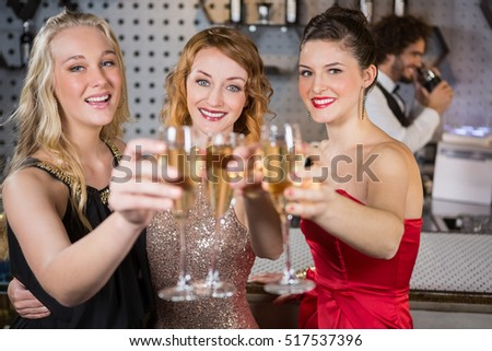 Portrait of three smiling friend showing glass of champagne at bar