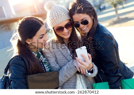 Portrait of three students girls using mobile phone in the campus. - stock photo