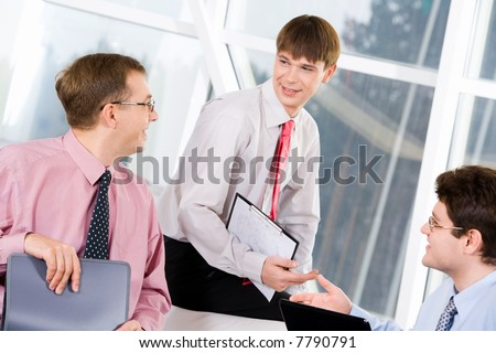 Portrait of three successful men chatting at business meeting