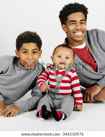 Portrait of three widely-spaced brothers -- An older teen,  an elementary boy and their baby brother.  On a gray background.