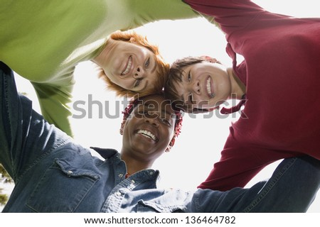 Portrait of three women in huddle - stock photo