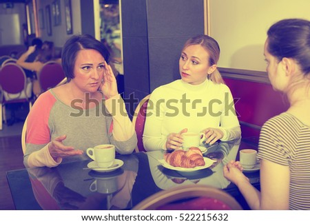 Portrait of three worried woman sitting in the cafe and talking with each other women