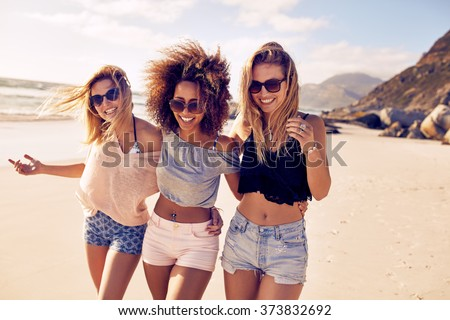 Portrait of three young female friends walking on the sea shore looking at camera laughing. Multiracial young women strolling along a beach. - stock photo