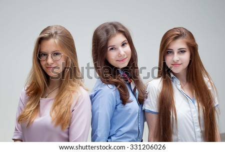 Portrait of three young pretty smiling students - stock photo