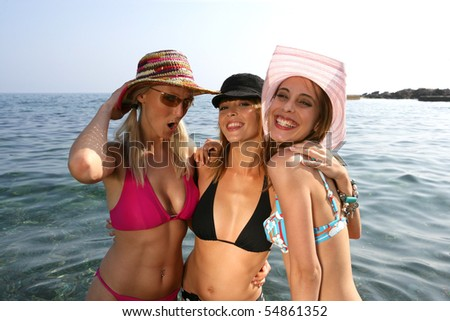 Portrait of three young women bathing in the sea - stock photo