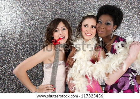 Portrait of three young women having a party and blowing whistles against a silver background. - stock photo
