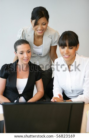 Portrait of three young women smiling in front of a computer