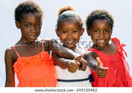 Portrait of threesome African girls doing thumbs up together.Isolated against light background. - stock photo