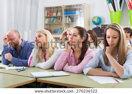 Portrait of tired adult students sitting at lesson in classroom - stock photo