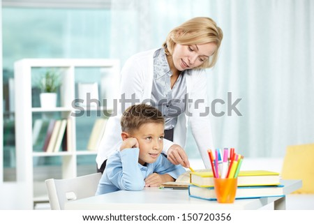 Portrait of tired boy and his tutor explaining something near by - stock photo