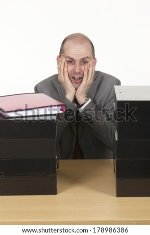 Portrait of tired businessman sitting with folders on his table