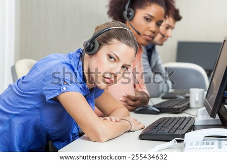 Portrait of tired female customer service representative with colleagues at desk - stock photo
