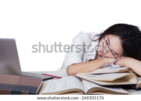 Portrait of tired female student sleeping above textbooks on desk, isolated on white