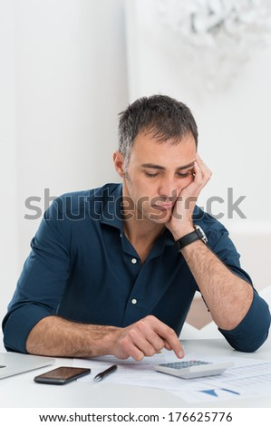 Portrait Of Tired Mature Man With Documents Using Calculator - stock photo