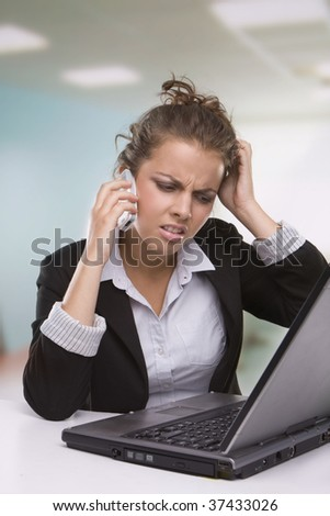 Portrait of tired secretary working in office speaking over the phone and using laptop