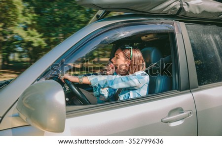 Portrait of tired young woman driving car and yawning after too long travel. Risk and danger at the road concept. - stock photo